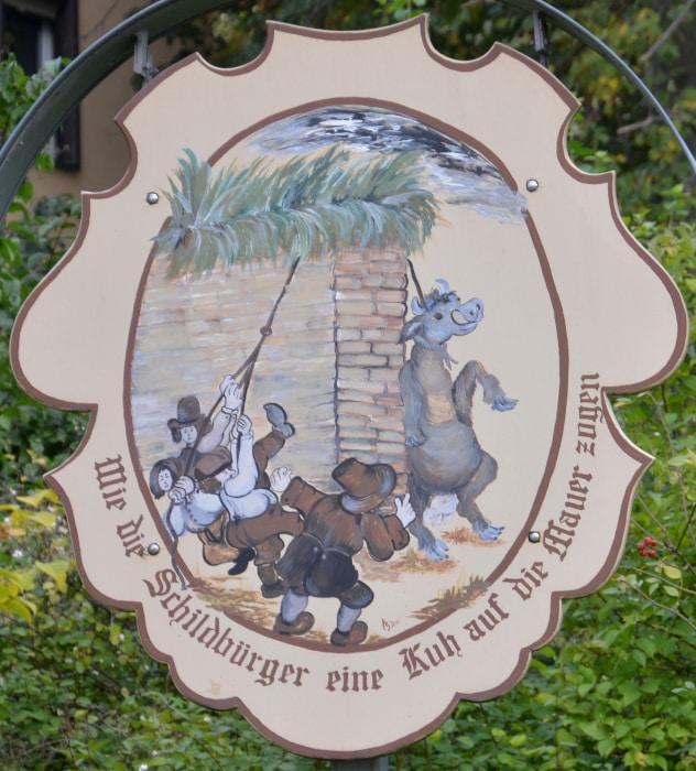 Schildau - Stadt der Schildbürger - Kuh auf die Mauer ziehen